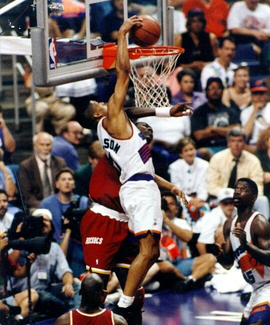 Kevin Johnson dunks over Hakeem Olajuwon during a playoff game in Phoenix.