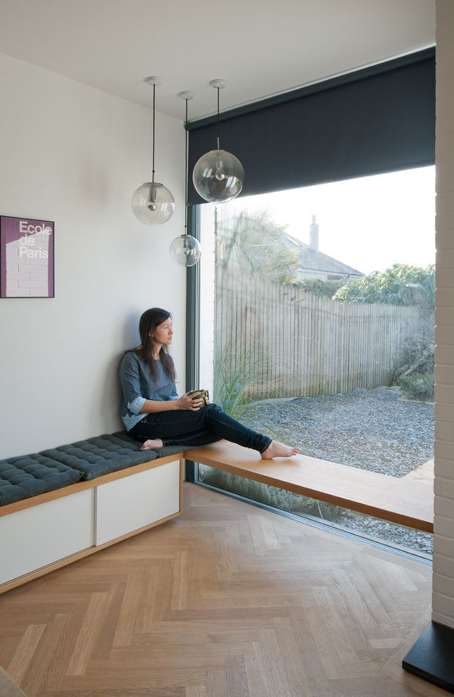 A built-in bench by the window is a cozy perch for Tyler. The herringbone flooring looks like wood but is actually man-made.