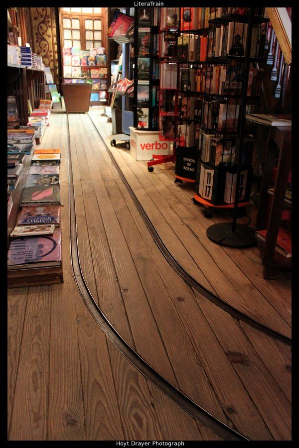 livraria lello in porto, portugal. it has train tracks running through it to carry books through the bookshop.