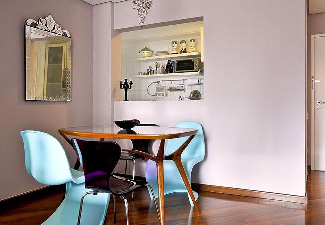 Cadeiras de diferentes modelos, mas da mesma cor, compõem esta sala de jantar aberta para a cozinha. Repare como elas se destacam da mesa de madeira clara
