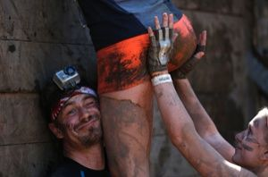 Arnsberg, Germany: Competitors climb over a wall at the Tough Mudder endurance event.