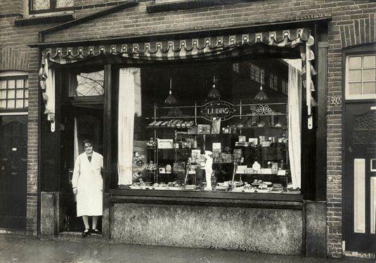 Gezicht op de winkelpui van Winkel no. 13 van de Lubro Brood- en Banketbakkerijen (Amsterdamsestraatweg 390) te Utrecht, met in de deuropening waarschijnlijk winkelhoudster mevr. Reitsma.1925