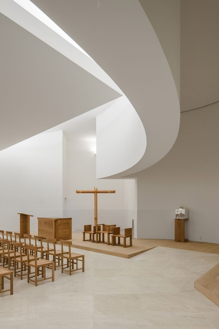 The crucifix is positioned in a chapel diagonally opposite the main staircase, which determines the axis of the congregation area and the orientation of the rows of custom-made seats.