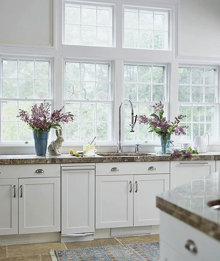 Kitchen Windows            A trash compactor and dishwasher, both faced with wooden panels to match the cabinets, flank the deep sink, which has an extra-tall spray faucet. Brushed nickel hardware adds a sleek, contemporary accent to the classic white cabinets