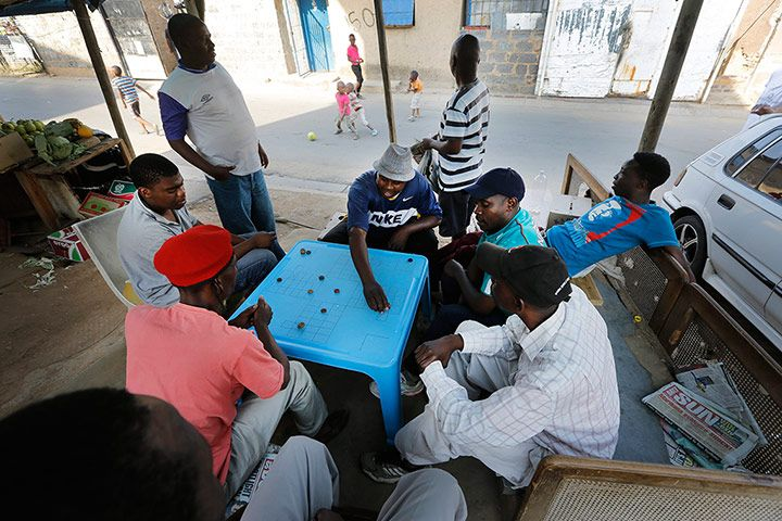 Men play a communal board game after work. Dwellers here enjoy an open society: children play outdoors, adults take part in dice and card games, and a wide array of small businesses thrive. Credit: Kim Ludbrook/EPA
