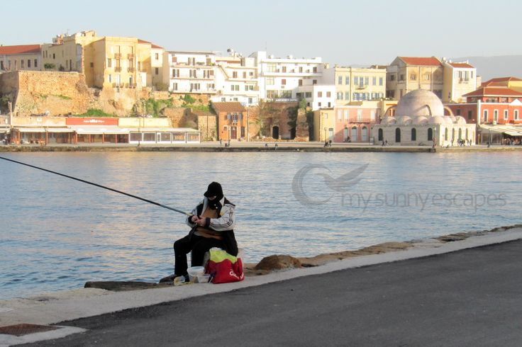 Chania, Crete: A fisherman at the old Venetian Harbour of Chania.