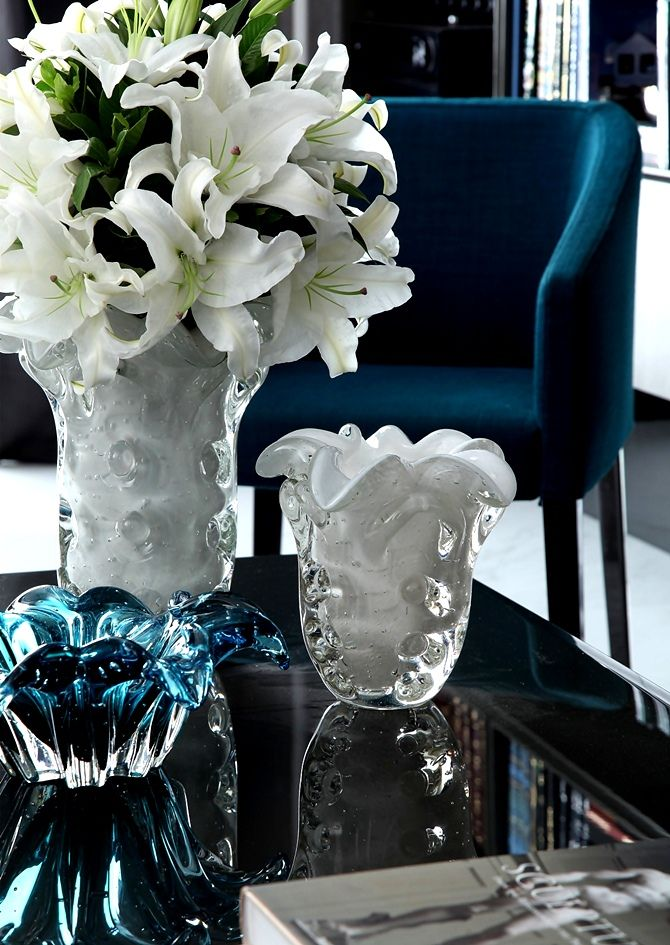beautiful coffee table arrangement with white Venetian glass vases and beautiful blue glass bowl;design by Christina Hamoui