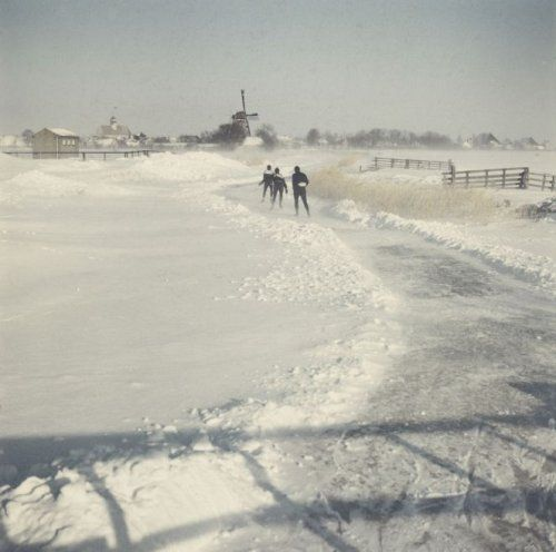 Elfstedentocht 1963. Drie deelnemers, zojuist een molen gepasseerd, schaatsen door het barre weer naar het volgende dorp, in een sneeuwlandschap. Friesland, Nederland, 18 januari 1963.