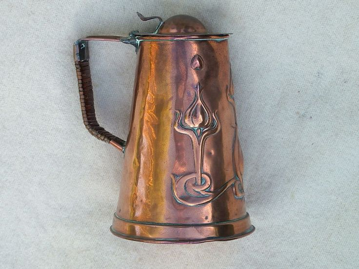 """This is a copper hot water jug in """"art nouveau"""" style by Joseph Sankey & Sons of Bilston, Staffordshire. The handle is wrapped with split cane. The body is decorated with typically stylized art nouveau floral forms. 