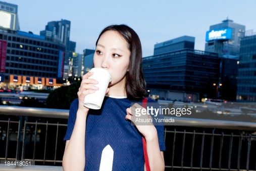 Stock Photo : Young woman drinking coffee in city location