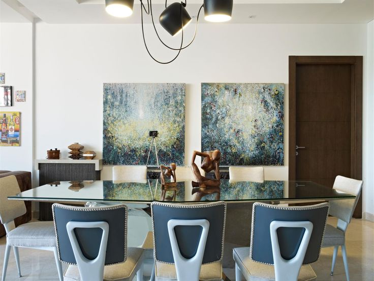 An Open Dining Room With View Of A Seating Area Glass Topped Table Reflects Artwork On Back Wall Matching Wooden Sculptures Serve As Centerpiece For The
