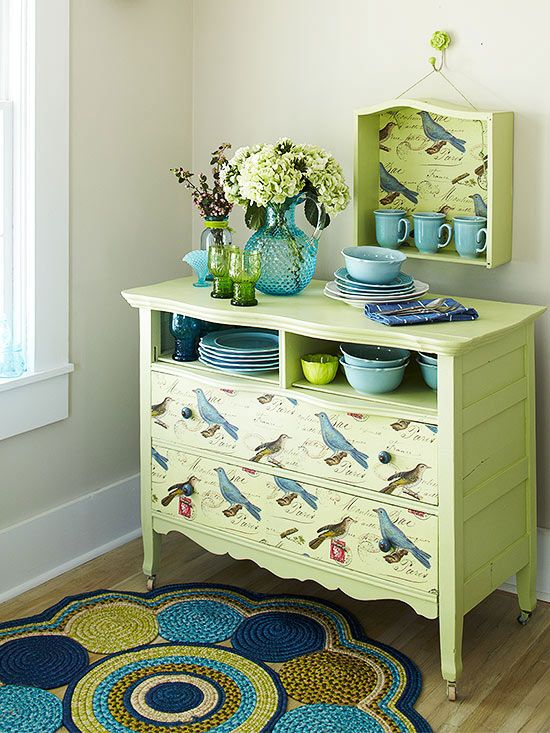 Convert a dresser into a buffet with paint and decorative paper. Create open display space by removing the top drawers and covering the cavities with plywood. For a fun twist on a traditional shelf, line the interior of one of the removed drawers with paper and hang it above the buffet. Secure paper to drawers with wallpaper paste.