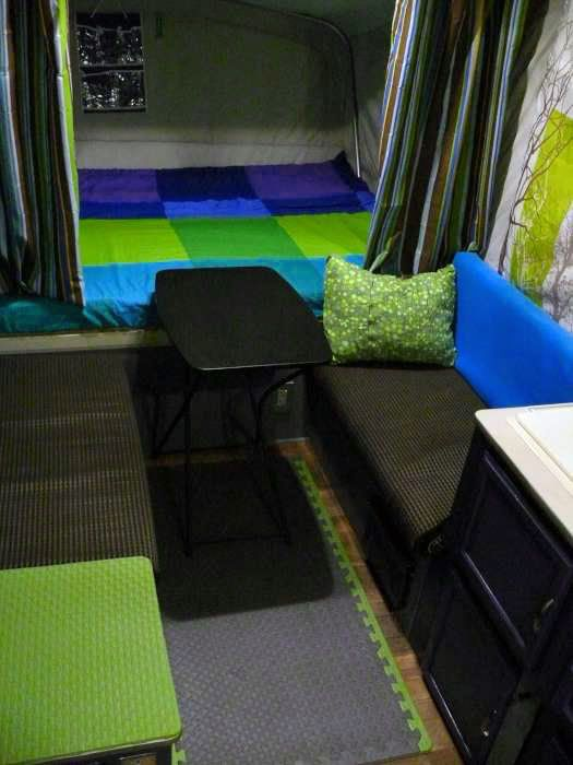 AFTER - Since we won't be using the dinette table to make a bed, we swapped it out for a smaller folding table that still has room for two. Duvet covers are from IKEA. Brown striped privacy curtains were a clearance find at Christmas Tree Shop for less than $1 a pair. The hanging organizer is from the Dollar store. The cute green pillow is a Thermarest camping pillow that squishes up into a small self-storing pouch.