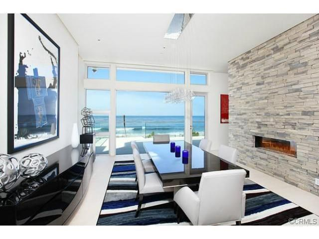 This Laguna Beach Dining Room Has A Stacked Stone Wall With Linear  Fireplace, Glossy Dining Table, Matching Console, White Fabric Chairs,  Striped Area Rug ...