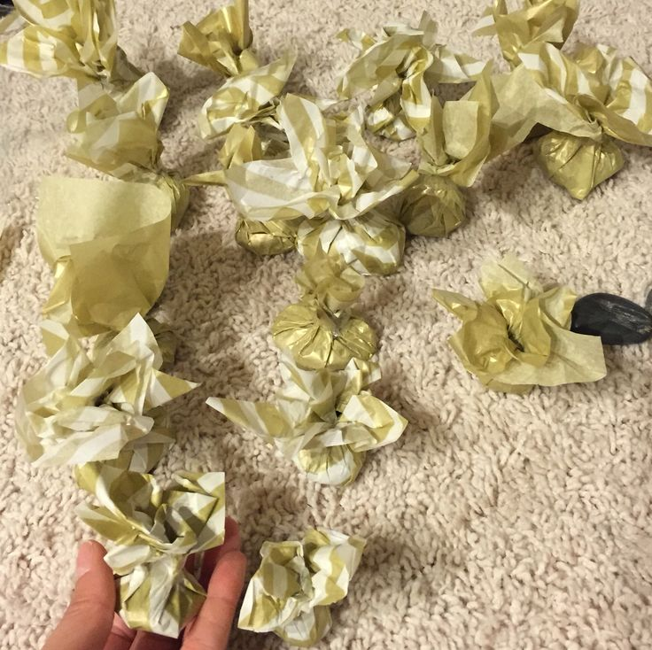 DIY balloon weights. I used tissue paper to wrap river rocks and used them as balloon weights to go with the theme. Blue, white and gold. - (update ... use something stronger than tissue paper if doing it outside , the wind will move them around and the ground will rip the paper)
