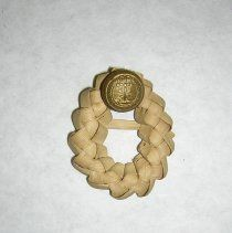 The secession badge is a small palmetto wreath with a South Carolina button attached to the bottom. This badge was originally attached to a piece of paper with a handwritten history. Dimensions: 1.5X1.25 inches This secession badge is one of the original South Carolina badges given to the donor, Miss Kinnie E. Smith, at Easter 1861, while she was attending school near Washington, D. C.