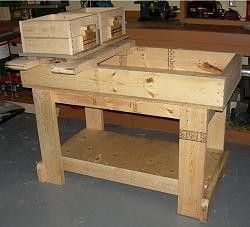 """Molding Bench by Carlos B -- Before you can mold patterns you need a bench to mix, hold and fill your mold flasks with molding sand. To that end I built this molding bench it is 2' X 4' and built very heavy with construction grade lumber and 3/4"""" plywood. It will hold 200 lbs of molding sand and 300 lbs in 5 gallon pails underneath. The roll over rails easily slide out for access to all the sand when mixing. And here are some pictures of my casting setup. First setting up for aluminum…"""