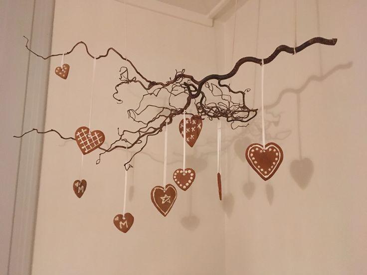 En gren av trollhassel med hjemmelagde pepperkaker pynter opp i et hjørne i spisestua