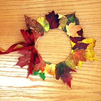 "Fall leaf wreath. Uses paper plate ""form"", glue, and leaves."