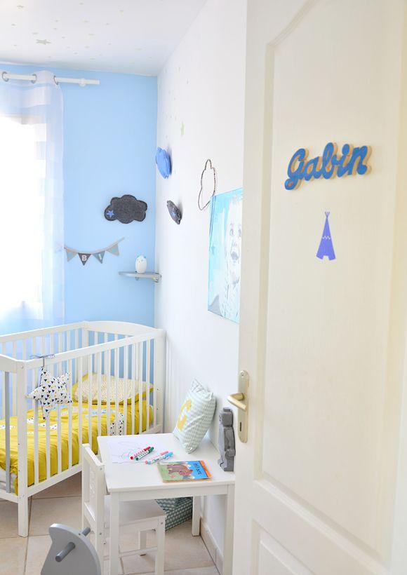 Une chambre bébé bleue avec des touches de jaune et de blanc