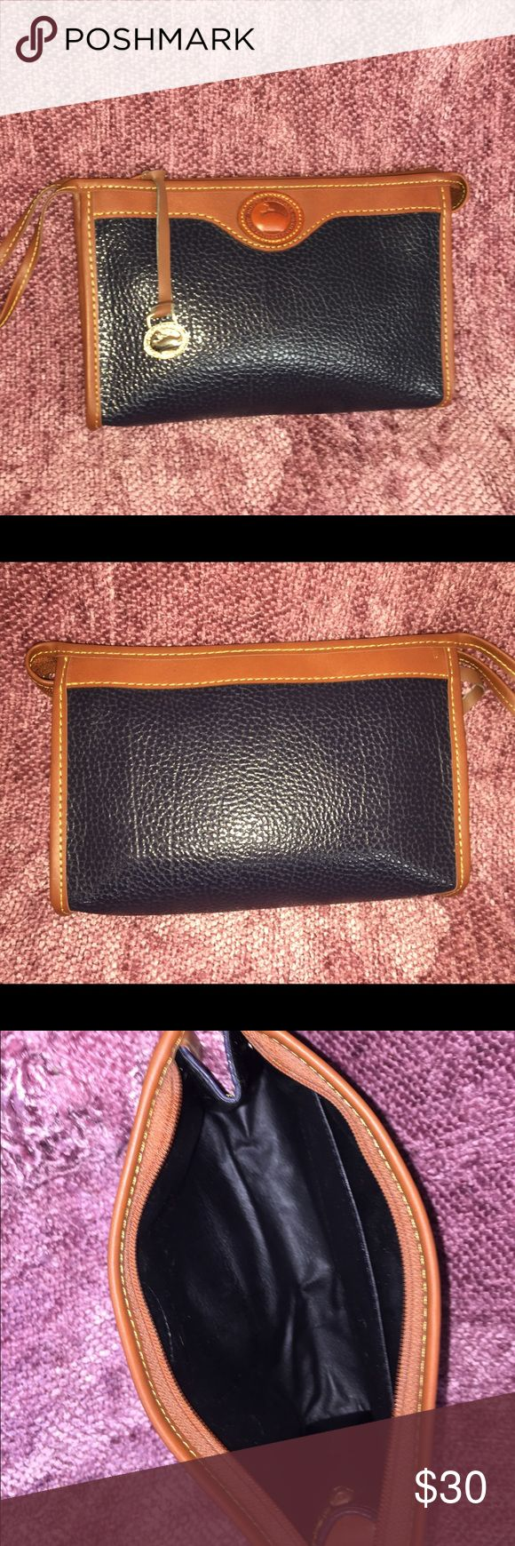 Dooney & Bourke clutch wristlet navy and brown 💙 Dooney & Bourke All Weather Leather clutch wristlet. Navy and brown. Wear on back of zipper pull-see picture. Otherwise in excellent condition. 🦆. Dooney & Bourke Bags