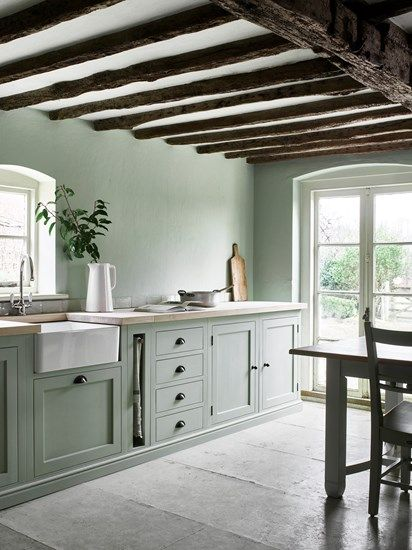 Green color + farm house sink + light floors + exposed beams