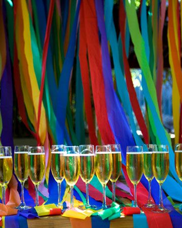 Glasses of sparkling cider rest in front of a rainbow backdrop made from strips of tablecloths