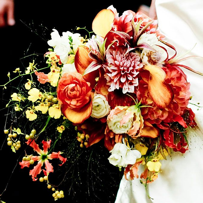 Brides.com: . Arrangement of gloriosa lilies, orchids, bittersweet berries, dahlias, ranunculuses, calla lilies, spider amaryllis, blushing bride proteas, and freesias. Bouquet by Waterlily Pond