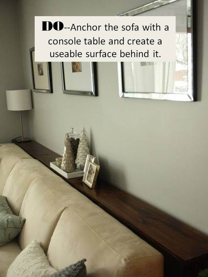Anchor a sofa with a console table and create a usable surface behind it.