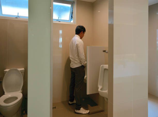 an asian business man urinates in bathroom person