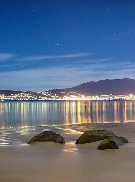 The lights of Hobart reflected in the Derwent Estuary below Kunanyi, Mt Wellington Tasmania, Australia.