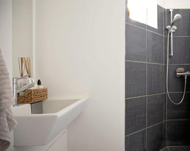 Badet er innredet i hvitt og grått. Varme tilføres interiøret via naturelementer som flettekurver og duftpinner.