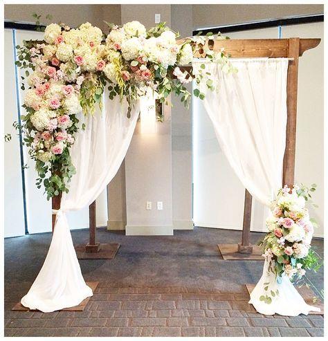 Beautiful wedding pergola debated with flowers and draping