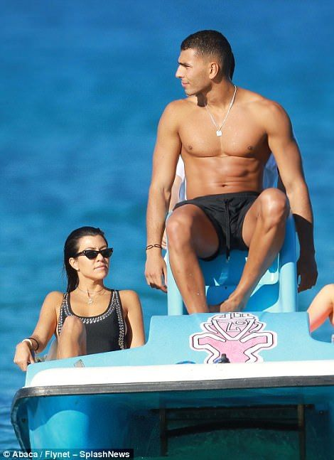 Chilling out: With her hair remaining wet from a paddle in the sea and sporting minimal make-up, Kourtney proved her striking natural beauty and clear, glowing skin as she relaxed aboard a pedalo with her man