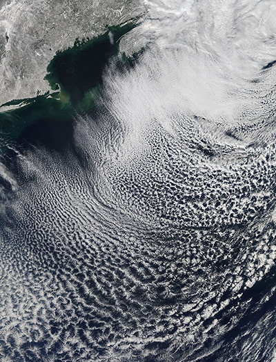 While New England dug out from the blizzard of 2013, clearing skies over the snow-laden land gave way to a beautiful pattern of cloud streets just off shore, on 10 February. Cloud streets form when cold air move over warmer waters, while a warmer air layer (a temperature inversion) sits over top of both. The streets (parallel lines of cloud) form along the direction of the wind. Newly formed streets appear well-defined and crisp...