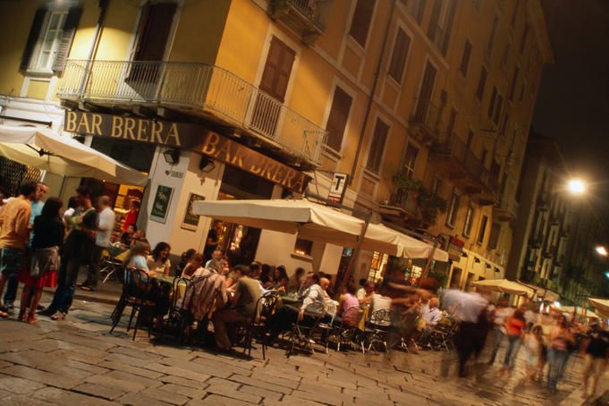People at outdoor tables of Bar Brera in Brera district at night. Milan, Italy