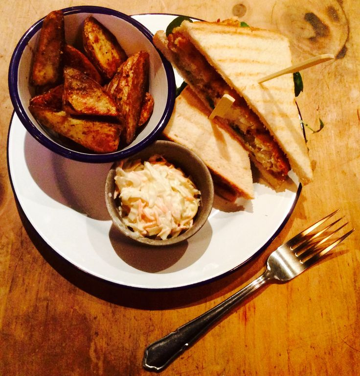 Fish finger buttie on toast with tartare sauce and rocket. Served with Cajun spiced wedges and slaw.