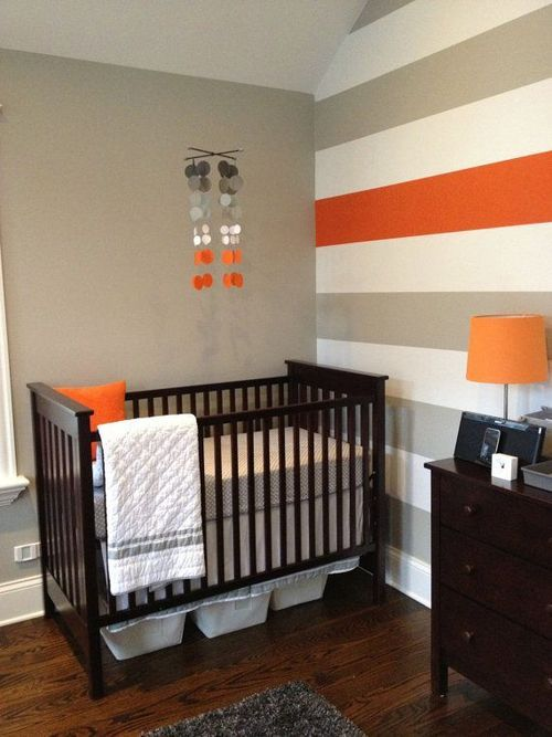 quarto de bebê decorado, parede de listras cinza e branco com uma faixa laranja, luminária laranja, berço e cômoda marrom madeira