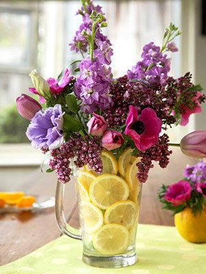 BHG has this really simple but very effective flower arrangement idea. All you need is a clear glass pitcher, a tall glass, some lemon slices and flowers.