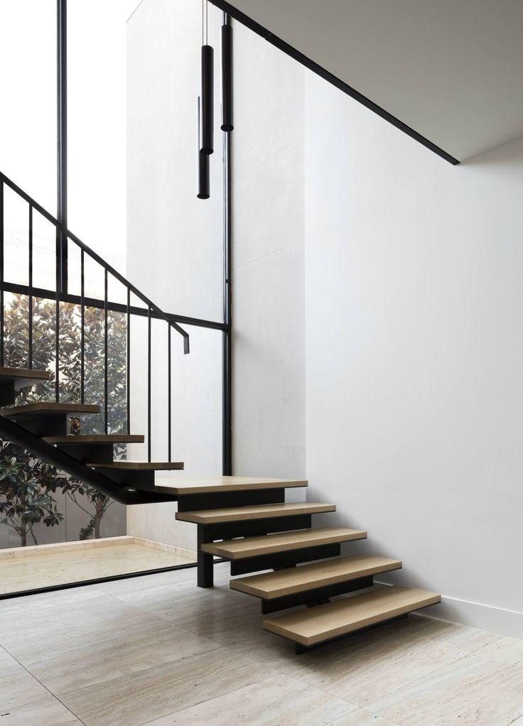Escada de aço preta, com degraus de madeira, esquadria com pé direito duplo. Casa Minimalista em Melbourne  por Davidov Partners Architects