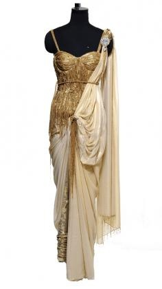 Golden Saree with flowing cream tones which is the subtle feature in this opulent and rich Saree by Raakesh Agarvwal.     Indian designer Raakesh Agarvwal concentrates his designs on glamorous, opulent, rich and complex garments in the categories Indian couture and ready to wear. Strand of Silk (strandofsilk.com) offers a gorgeous selection of Indian wedding ouftis: Bridal Sarees, Wedding Lehengas and Indian dresses designed by one of India´s most notable designers Rakesh Agarvwal.