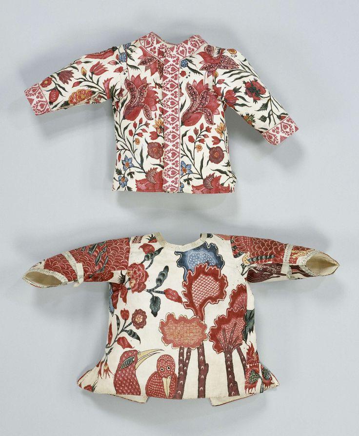 Kinderjas of jakje van sits, dat op een wit fond florale motieven en twee vogels vertoont
