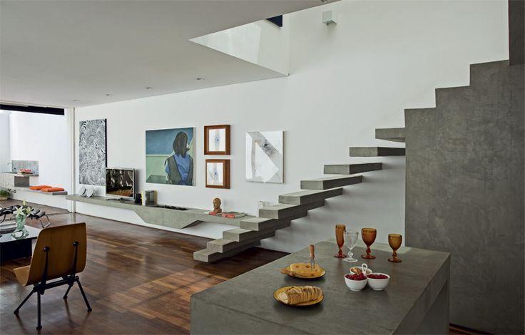 Acabamentos neutros – como os tacos de cumaru (Pau-Pau Pisos de Madeira), a escada de concreto e a pintura branca – destacam as obras de arte.