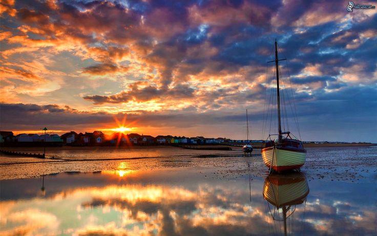 Spiaggia al tramonto, barca a vela, nuvole, deflusso