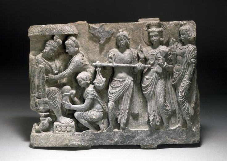 Panel showing the Bodhisattva as King Śibi ransoming a pigeon with his own flesh. From right to left a youthful haloed deity with moustache and a chignon bound at the base stands almost in profile with his right hand raised, palm outward. He wears a paridhāna and uttarīya, a collar with small pendants and double bracelets, that on his left wrist beaded and with discs. Beside him