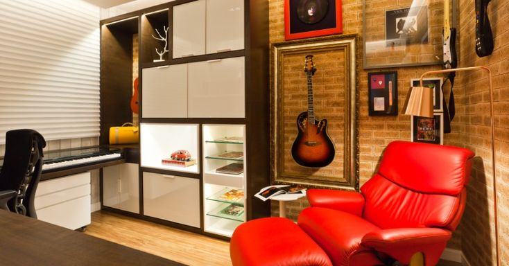O estúdio faz parte do apartamento de um fã de rock; acomoda mesa, duas guitarras e teclado em móvel retrátil, com gaveta deslizante e tampo de vidro.