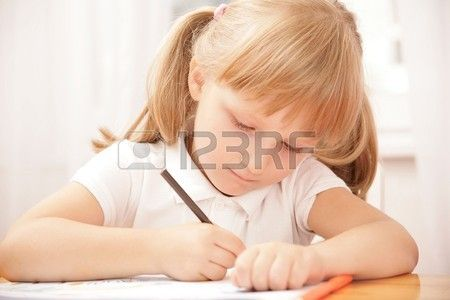 Portrait of serious girl writing something in copybook