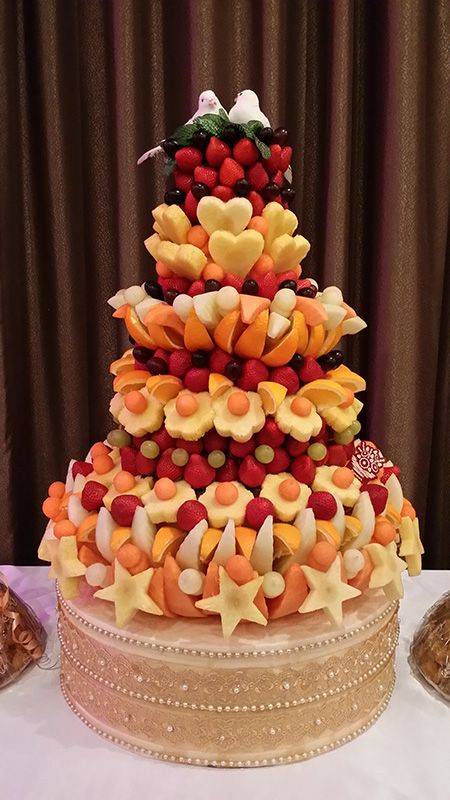 Fresh Fruit Tower  A perfect centerpiece for any ocassion, Engagements, Weddings, Brithdays, Company parites, Christmas parties.  Stunning and eye catching piece to art work which will woo all your guests on your very special day. 60cm tall cone tower, filled with fresh fruit cut to size and pieces. Ideal upto 100 guests.