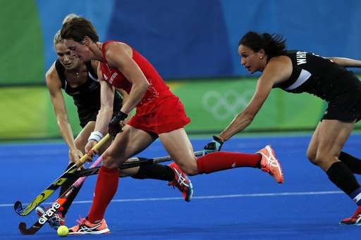 Britain's Hannah MacLeod, center, fights for the ball with New Zealand's Stacey Michelsen during a women's field hockey semifinal match at the 2016 Summer Olympics in Rio de Janeiro, Brazil, Wednesday, Aug. 17, 2016.