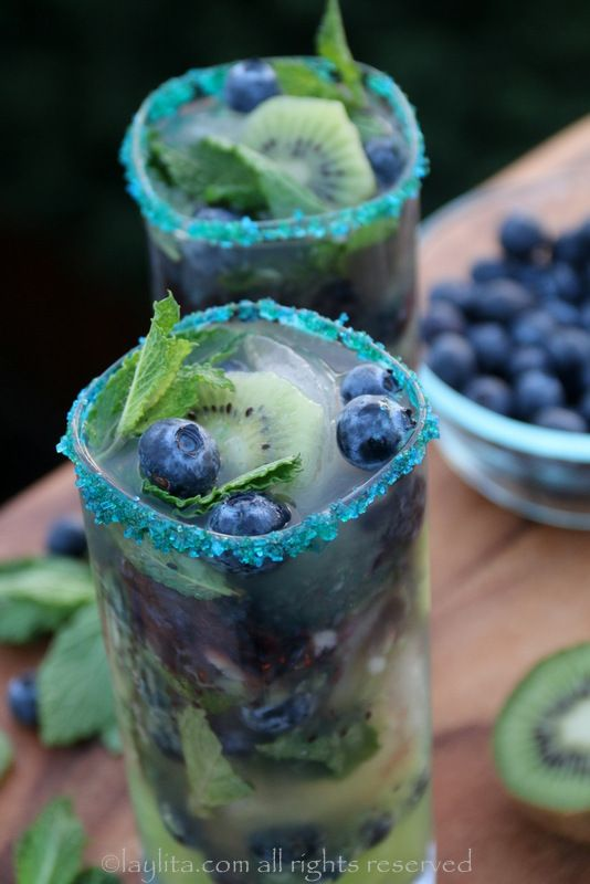 Kiwi Blueberry Mojito - made with fresh kiwis, blueberries, lime, mint leaves, sparkling water and rum. Garnish the glass rims with green or blue sugar - you can also use cookie or baking colored sprinkles.